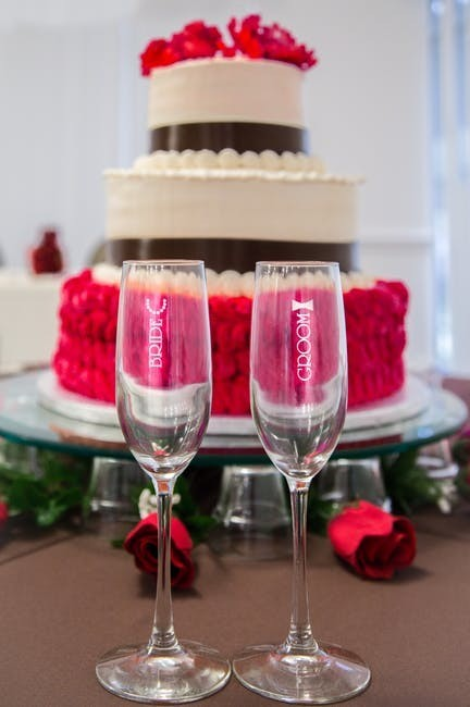 red and cream wedding cake with glasses in front