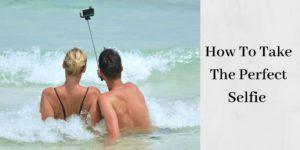 couple in ocean taking selfie