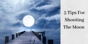 full moon over dock of lake