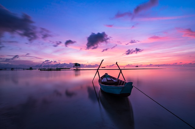 pink and purple sunset over boat in lake